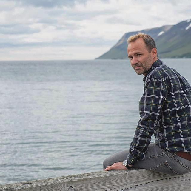 Hombre sentado en embarcadero Islandia